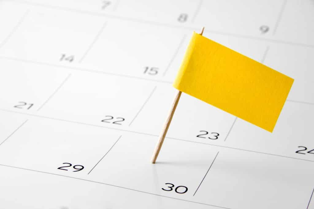 Yellow flag pinned on the calendar on the 30th day of the month