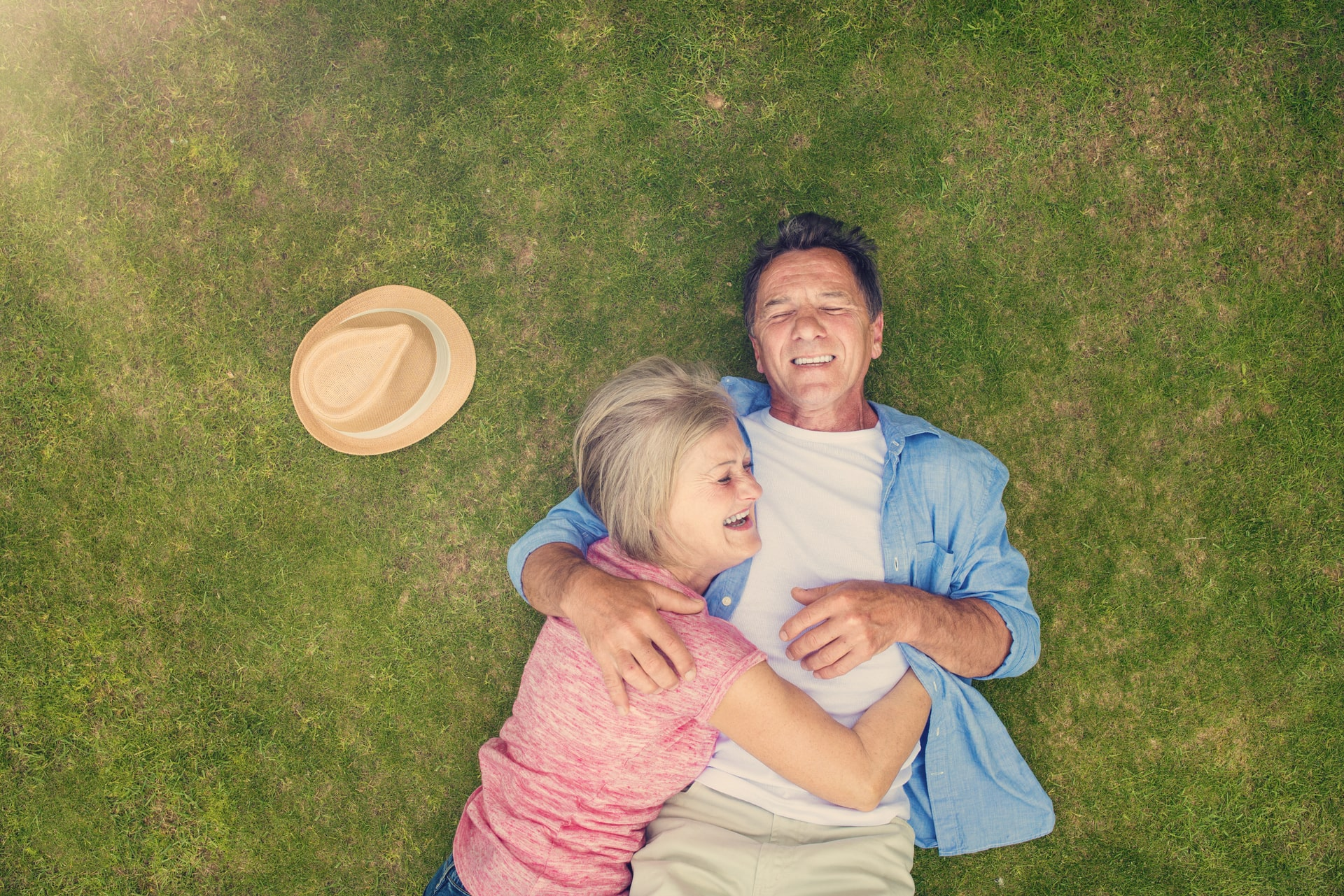 Old couple lying down on green grass smiling looking towards the sky and filled with happiness and joy