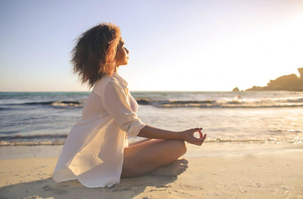 Girl outdoors on the beach sitting down and meditating