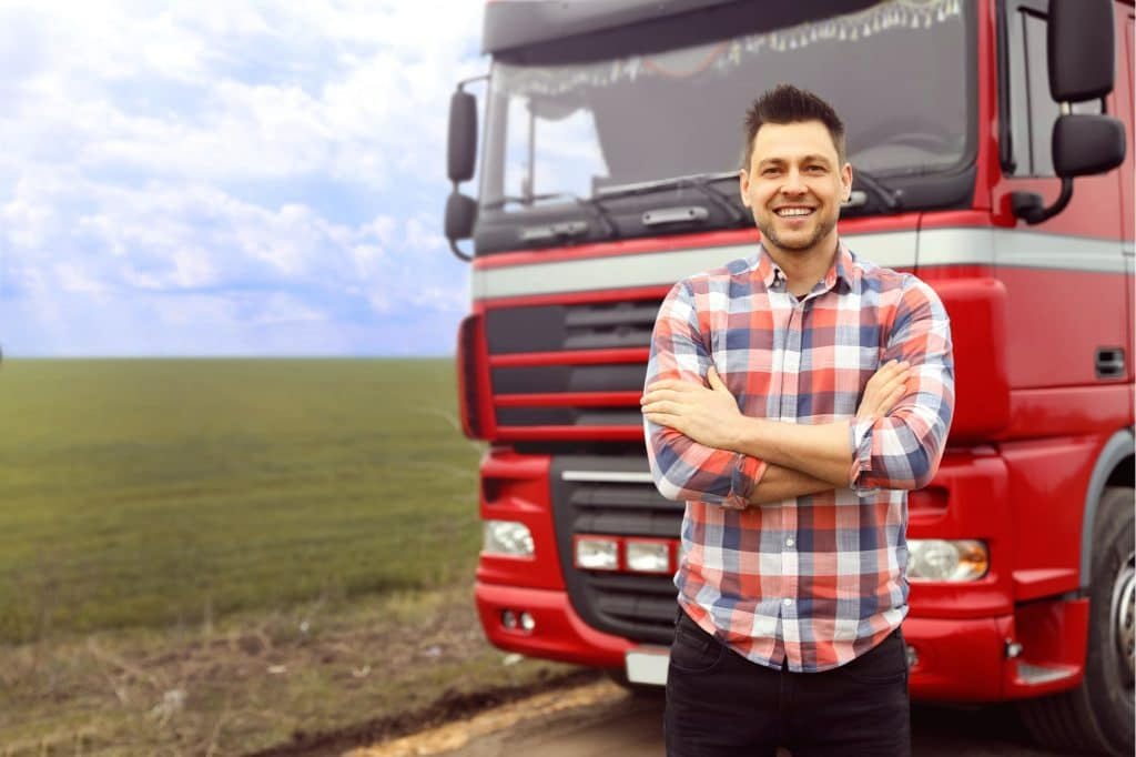 Truck driver standing in front of his red truck in the middle of a field